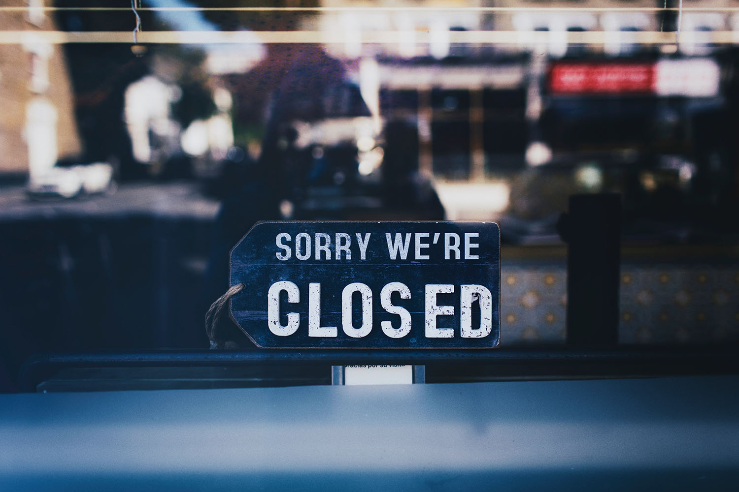 """""""Sorry we're closed"""" sign hanging in glass window"""