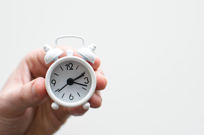 Hand holding mini white clock