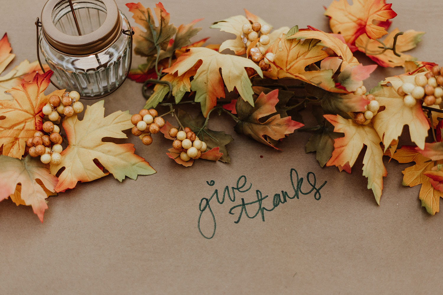 """Fall leaves on a table that says """"Give thanks"""""""